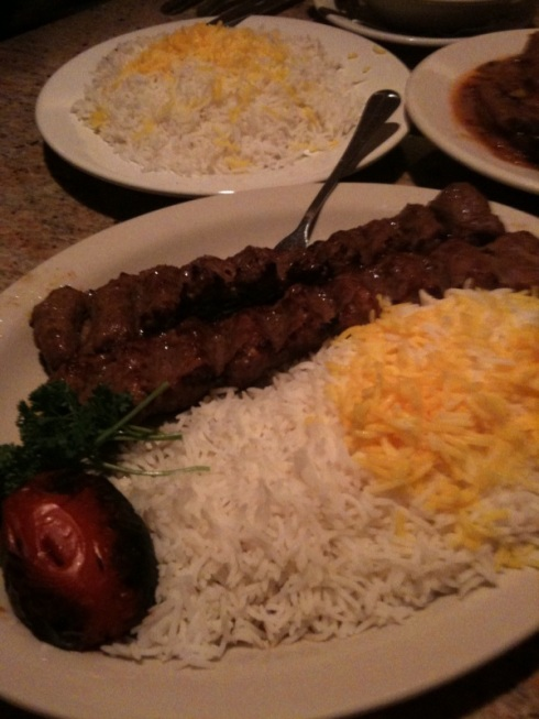 Beef kabab with rice and a grilled tomato